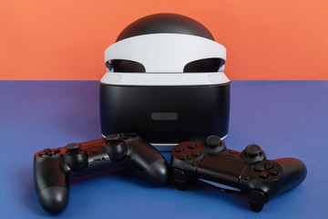 Game controller and virtual reality helmet on a red festive background.