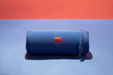 Blue wireless speaker on a bright red-blue background