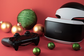 Game controller and virtual reality helmet on a red festive background. Christmas background