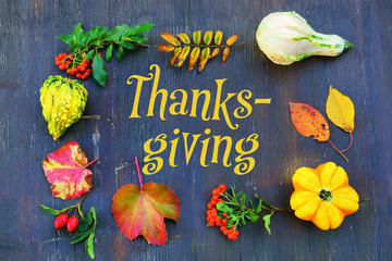 Thanksgiving background with pumpkins and leaves on old shabby board