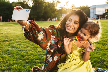 Mother with her little daughter take a selfie by mobile phone.
