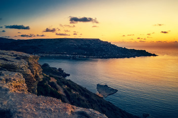 beautiful sunset and seascape view of Golden Bay, Malta, travel background