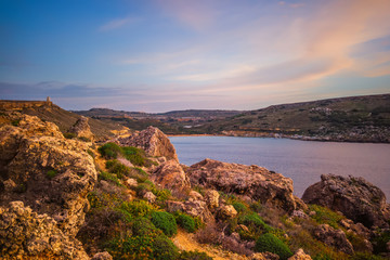 beautiful sunset and seascape view with mountains of Golden Bay, Malta, travel background