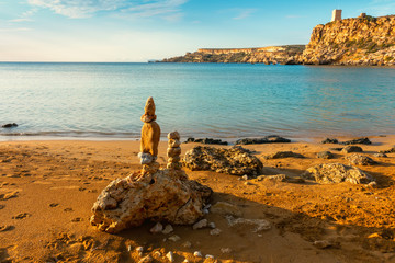 beautiful seascape scene of stones pyramid on beach at sunset, rest and seaside vacation concept, Malta