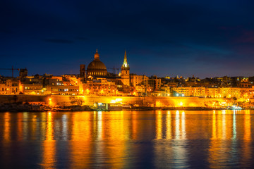 beautiful view in front of night scene of Basilica Our Lady Mount Carmel in Valletta from Sliema, Malta