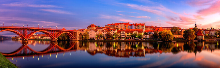 Amazing view of Maribor Old city, Main bridge (Stari most) on the Drava river before sunrise, Slovenia. Scenic cityscape with sky and reflection, travel background for wallpaper or guide book