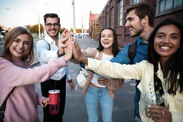 Group of friends stacking hands outdoor - Happy young people having fun joining and celebrating together