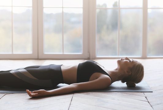 Yoga still girl laying on sport mat, relaxing after exercising
