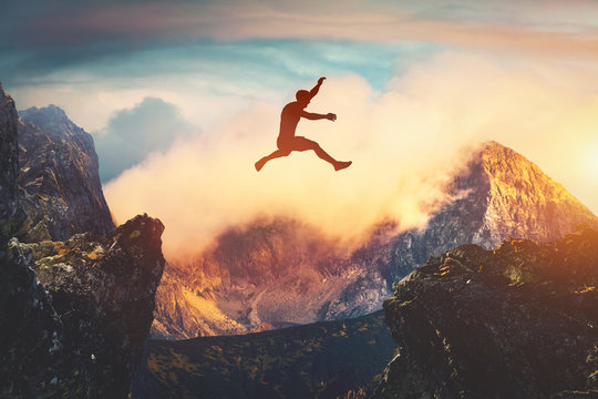 Man jumping between mountains at sunset.