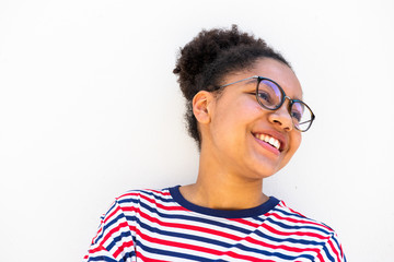 Close up of smiling young african american girl with glasses looking away by white wall