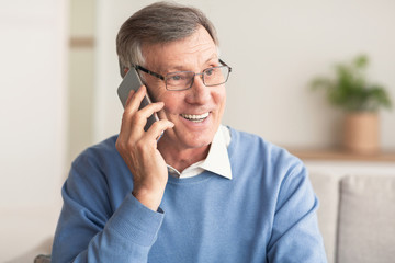 Elderly Man Talking On Cellphone Sitting On Couch At Home