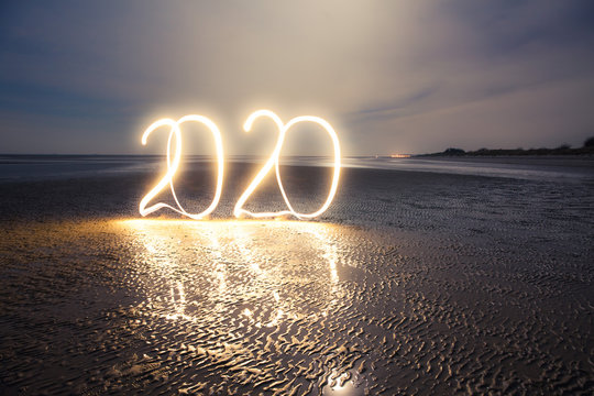Light painting for the New Year's celebration: Writing 2020 with light into darkness on a beach at low tide