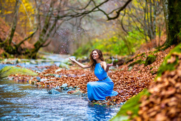 woman in blue dress near a river in autumn day