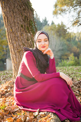 Girl with hijab, in long formal dress walking on grass, dry autumn, sunny day on the mountain, fallen leaves