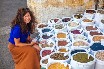 Woman sitting next to bags of spice
