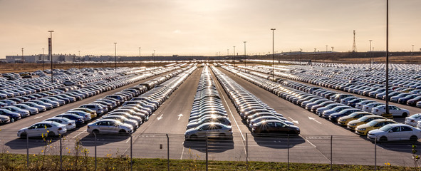 Volkswagen, Russia, Kaluga  - NOVEMBER 13, 2019: New cars parked in a distribution center on a sunny day in the autumn, a car factory. Panorama of a parking in the open air.