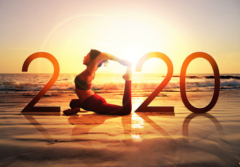Happy new year card 2020. Silhouette of healthy girl doing Yoga One Legged Pigeon pose on tropical beach with sunset sky background, woman practicing yoga as a part of the Number 2020 sign. Wall mural