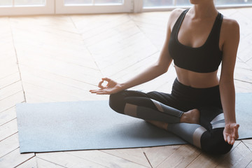 Cropped photo of fit girl sitting in lotus pose