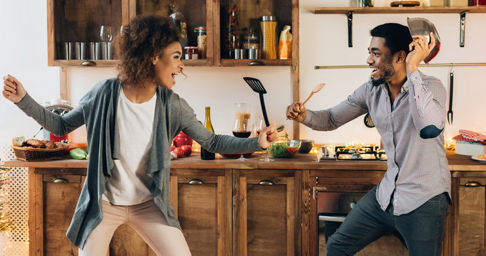 Funny couple fighting with utensils tools in kitchen