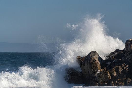 Large wave crashing onto jagged rocks in Monterey Bay, California