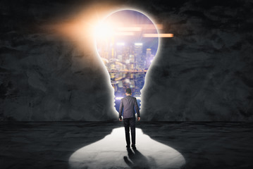 The double exposure image of the businessman standing in front of the door shape as the lamp during sunrise overlay with cityscape image. The concept of modern life, business, city life and future.