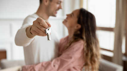 Happy couple hugging holding keys buy new apartment concept, closeup