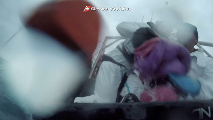 Italian coast guard members rescue a young migrant child from the Mediterranean after a boat capsized in this still image taken from a video