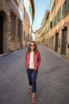 Happy young woman in typical Italian empty street.