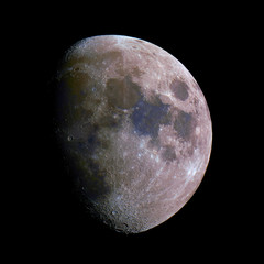 Waxing gibbous mineral Moon phase, isolated in the black space, with its natural colors, from red to blue.