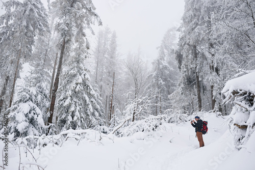 Fototapete Young man taking pictures of a snow covered forest