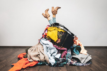 woman legs out of a pile of clothes on the floor. shopping addiction concept Wall mural