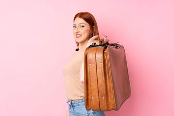 Young redhead woman over isolated pink background holding a vintage briefcase