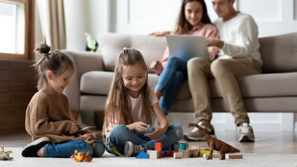 Happy kids playing while parents using laptop in living room