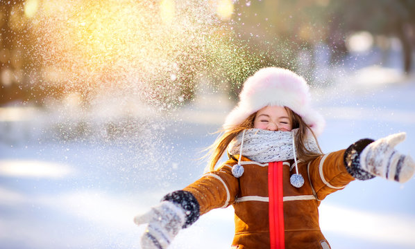 A girl walks in the winter forest, throws snow and has fun. Outdoor activities.