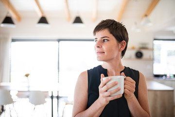 Front view of young woman with coffee standing indoors at home.