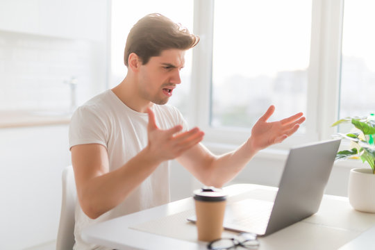 Entrepreneur angry and furious man with a laptop at home