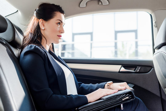 side view of attractive ambassador holding briefcase while sitting in car