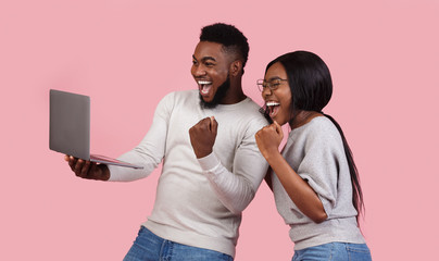 Happy black couple celebrating success with laptop