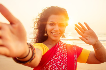 self portrait of gorgeous beautiful indian woman taking selfie photo with mobile phone camera in exotic tropical beach enjoying summer Goa beaches