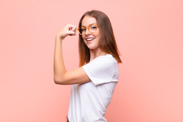 Fototapeta young red head woman feeling happy, satisfied and powerful, flexing fit and muscular biceps, looking strong after the gym against flat wall obraz