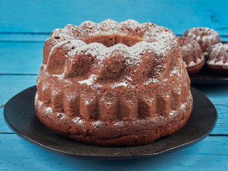 Homemade chestnut Bundt cake, dusted with sugar,  on blue wooden background