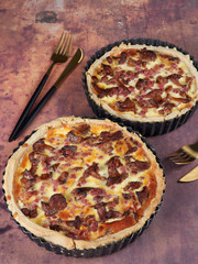 Homemade quiche with chanterelles and bacon, on brown background