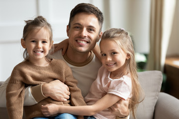 Happy young dad embracing cute kids daughters looking at camera