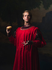handsome man in a Royal red doublet eating fast food