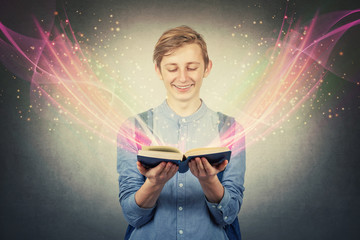 Overjoyed boy teenager smiling as holding a opened bewitched textbook. Magic book concept,...