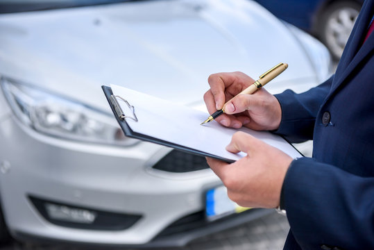 Male hands with clipboard against new car
