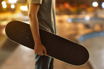 Man holding skateboard at skatepark