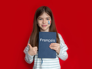 Portrait of a young girl with a painted French flag on her cheek on a red background. Learning...