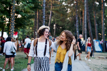 Portrait of two young women friends at summer festival, walking.
