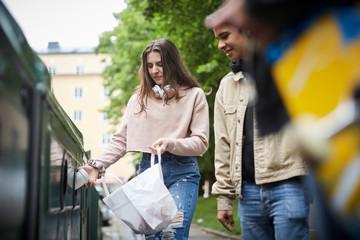 Smiling man looking at female friends throwing waste in garbage bin